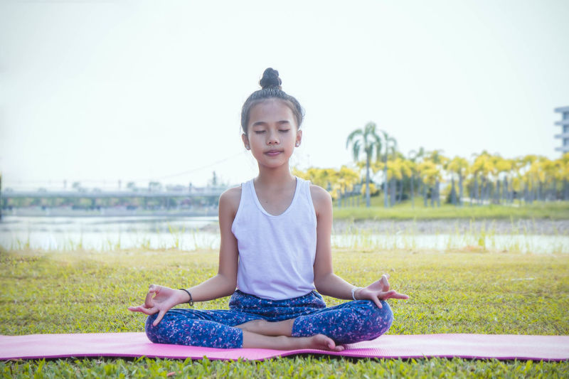 yoga girl's in the park Cross-legged Day Exercising Front View Full Length Grass Hairstyle Healthy Lifestyle Leisure Activity Lifestyles Looking At Camera Lotus Position Nature One Person Outdoors Portrait Real People Relaxation Exercise Sitting Sport Yoga