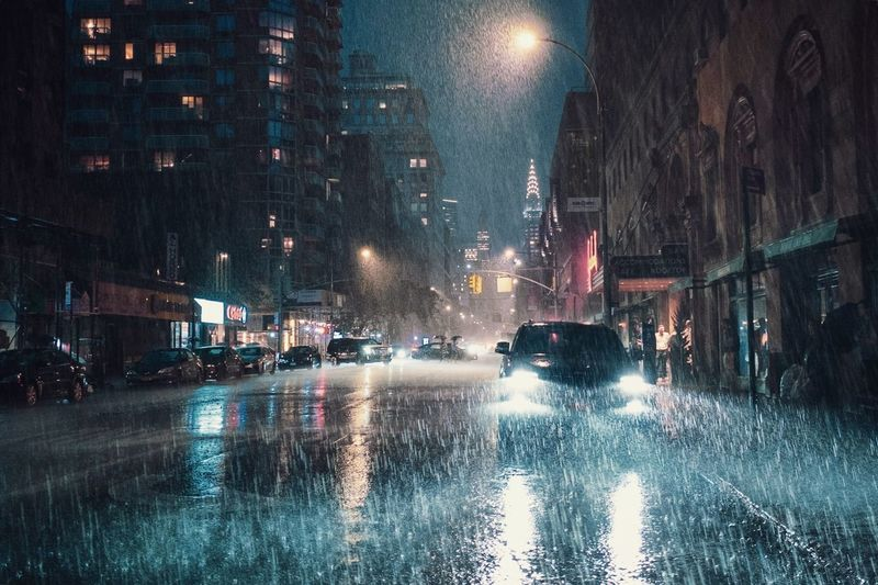 Cars on city street during rainy season at night