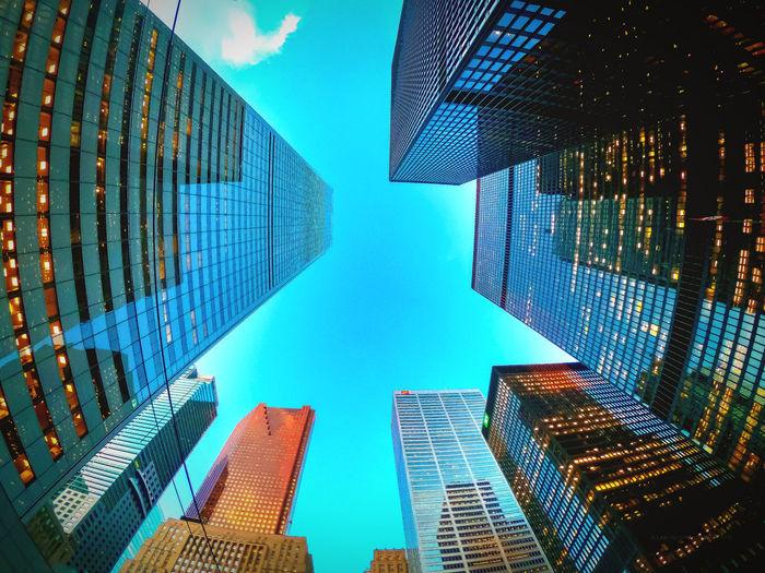 Directly below shot of modern buildings against blue sky