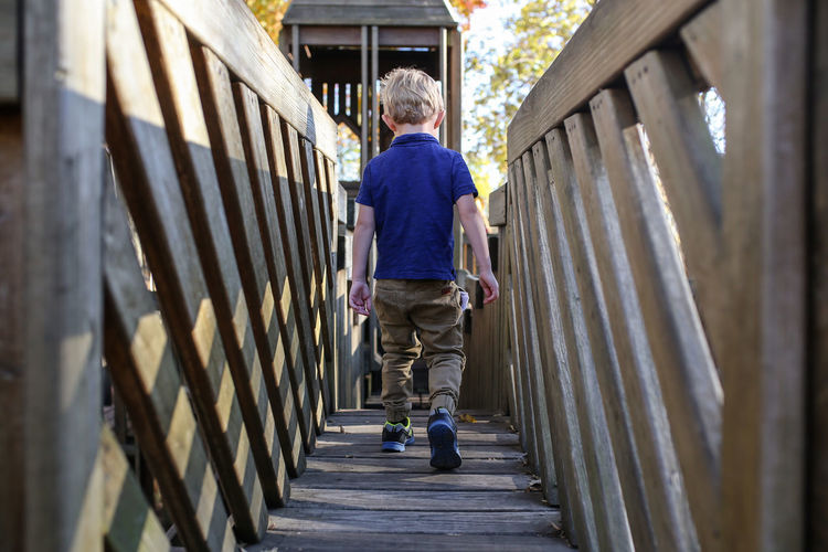 Boy walking over bridge of wooden playground Childhood Full Length Child Males  Boys One Person Casual Clothing Rear View Wood - Material Outdoors Innocence Wooden Playground Playground Playset Close-up Kids Childhood Memories Fall Beauty Autumn Fall Fun Bridge