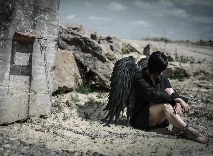 Woman wearing wings trapped with chain on land