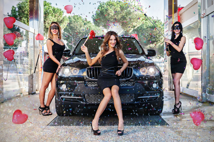 Three girls in a dark suit, posing in the mask in a box designed to hold the car wash to clean the car. We are in the month of February when we celebrate the carnival. Ballons Carnival Time Adult Beautiful People Beautiful Woman Beauty Car Carwashing Day Fashion Friendship Front View Full Length Girls Glamour High Heels Lifestyles Looking At Camera Outdoors People Portrait Real People Standing Young Adult Young Women