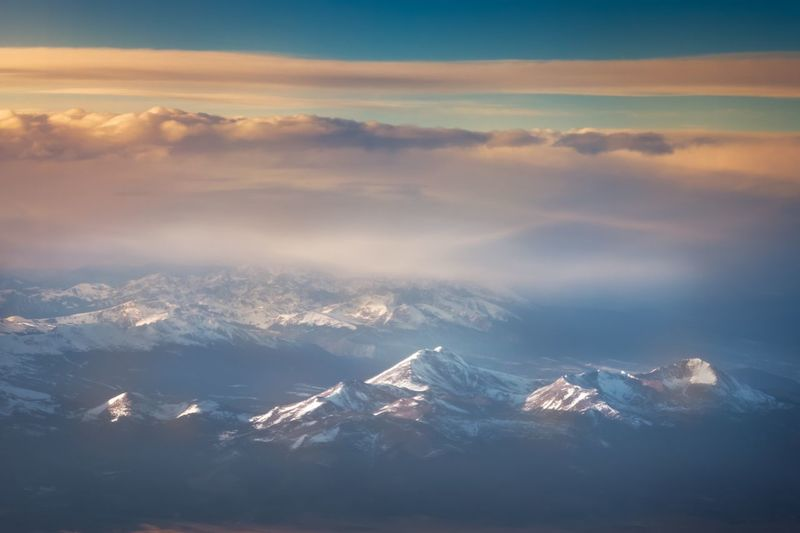 Aerial view of snowcapped mountains against sky during sunset