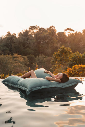 Woman relaxing on pool raft in swimming pool