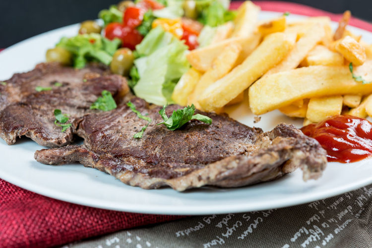 Beefsteak and french fries with salad and sauce served in plate