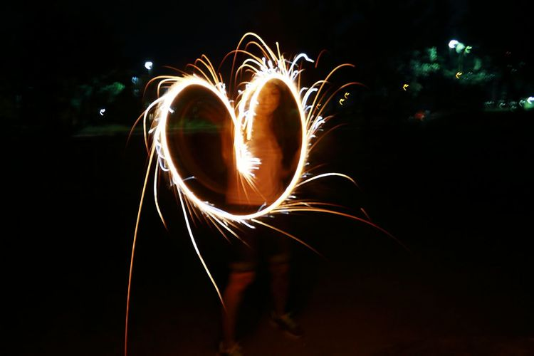 Young woman creating heart with sparkler at night