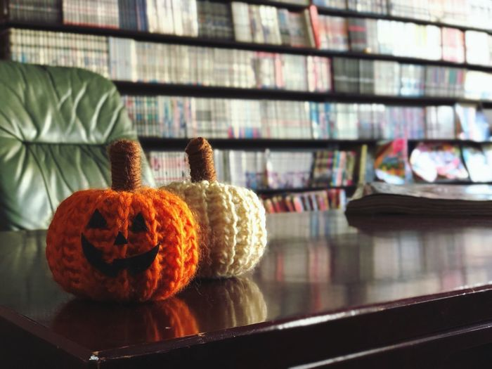 Close-up of halloween decoration on table against bookshelves