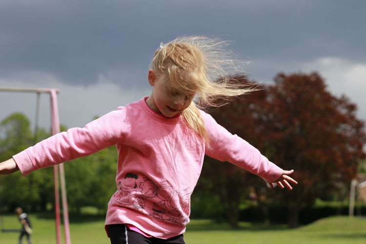Girl playing with arms raised against sky