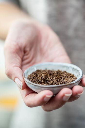 Close-up of hand holding cumin seeds