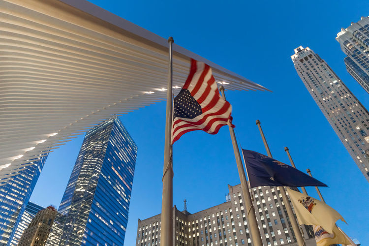 US flag waving against famous Oculus in New York City New York New York City Oculus Architecture Building Building Exterior Built Structure City Clear Sky Democracy Financial District  Flag Independence Low Angle View Modern National Icon No People Office Building Exterior Outdoors Patriotism Skyscraper Striped Sunlight Tall - High Wind