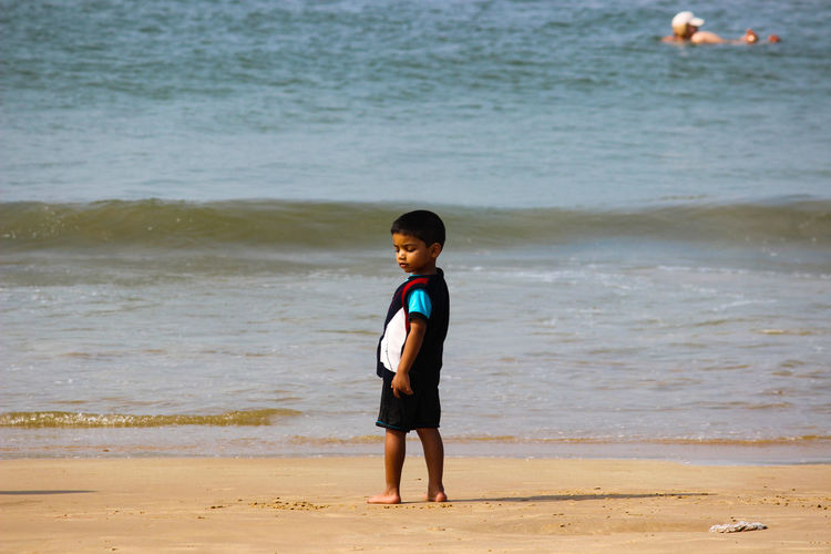 Full length of cute boy standing on shore at beach