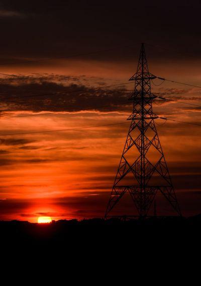 Silhouette electricity pylon against orange sky