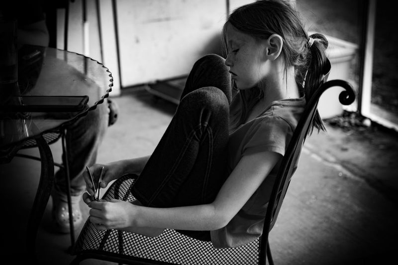 Side view of girl sitting on chair at home