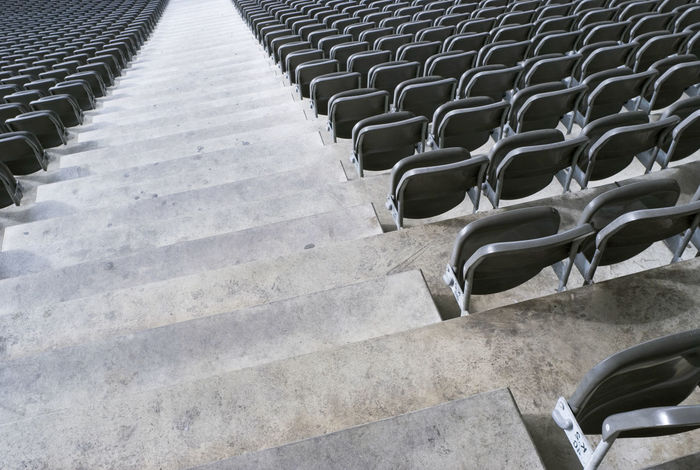 sitting area and concrete steps Steps Aisle Auditorium Chair Concrete Downward Empty Event Hall Folding Chair Grey In A Row Large Group Of Objects No People Passage Seat Seats Staircase