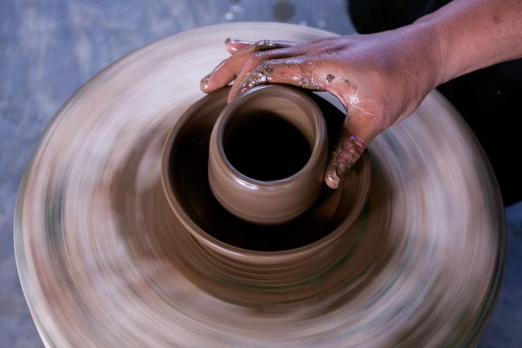 Cropped Hand Of Potter Making Pot At Workshop