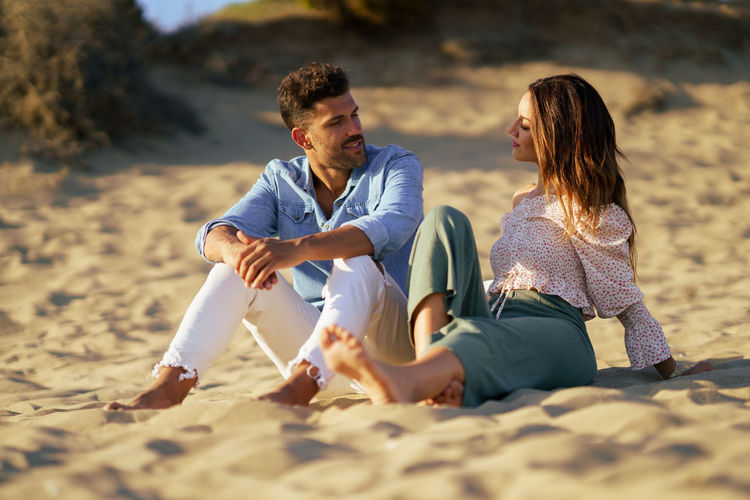 Couple talking while sitting on sand at beach