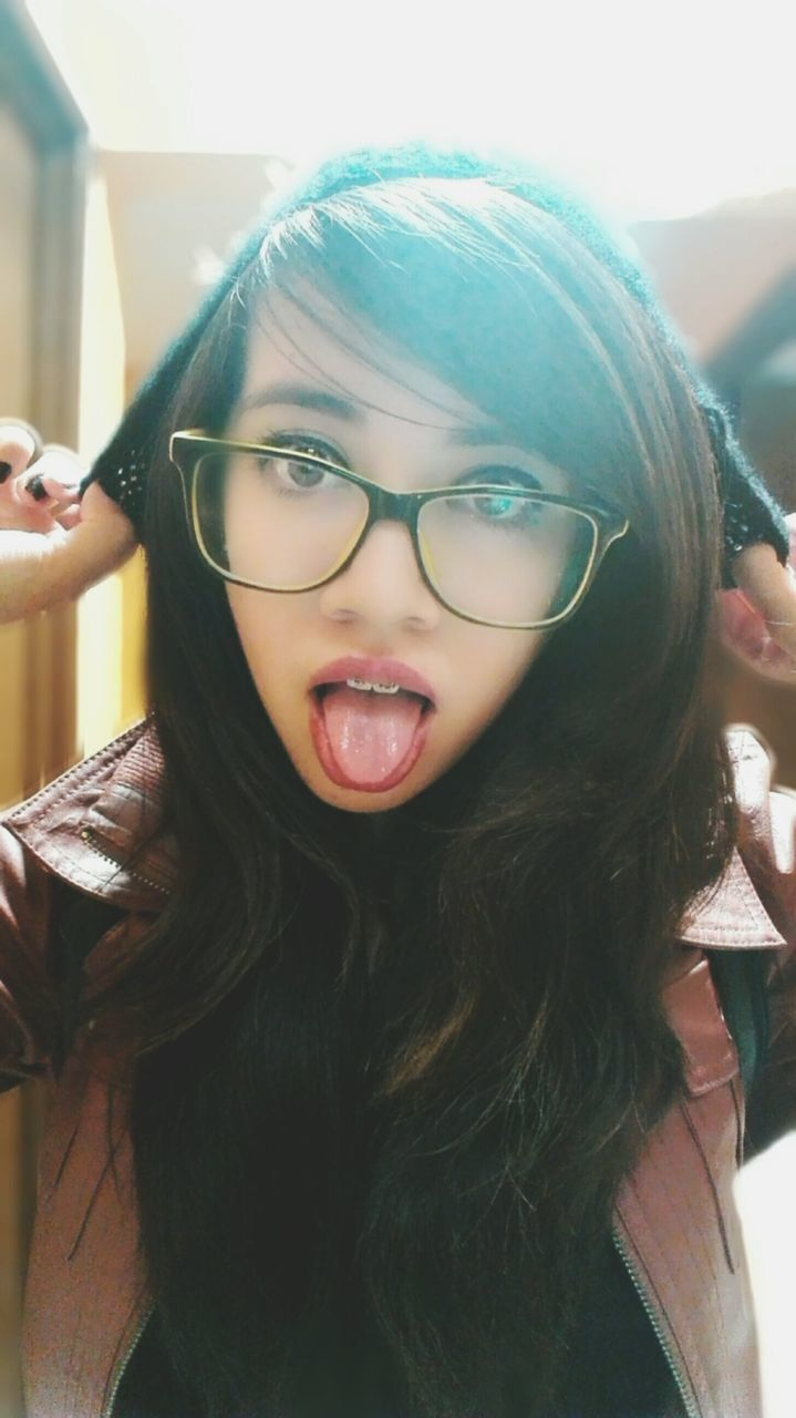 eyeglasses, real people, one person, looking at camera, front view, lifestyles, portrait, long hair, glasses, young women, leisure activity, young adult, focus on foreground, indoors, childhood, close-up, happiness, day, headshot, making a face, warm clothing