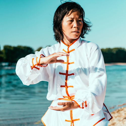 Woman practicing martial arts at lake against sky