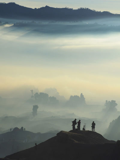 Silhouette People Standing On Mountain During Foggy Weather