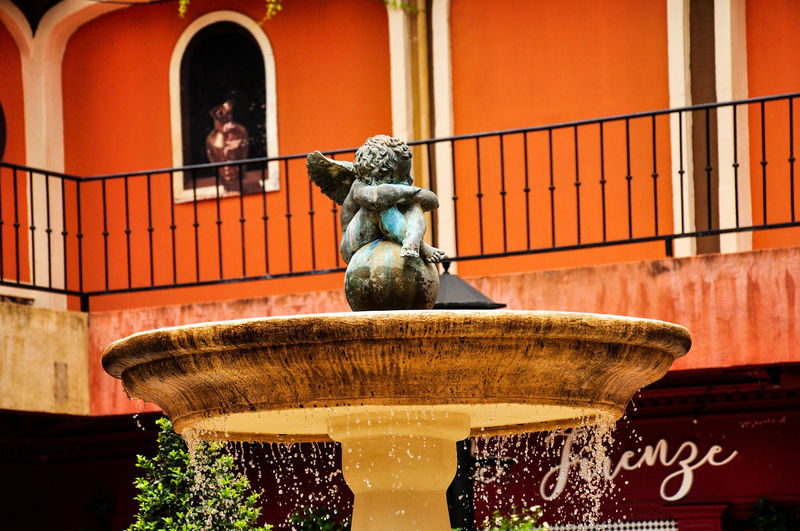 Statue of fountain against building