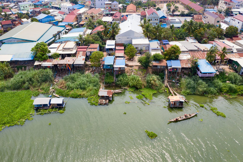 High angle view of houses by river and buildings