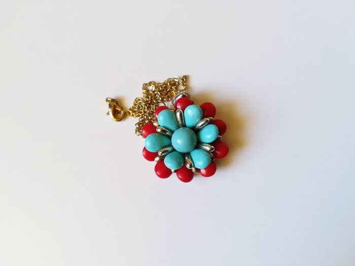 Refined Elegant Golden Necklace Torquoise Red Turquoise And Red Jewel In The Shape Of A Flower Pendant Necklace Candy White Background Multi Colored