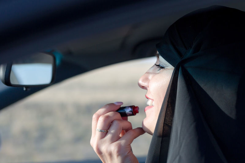Smiling woman applying lipstick while sitting at car