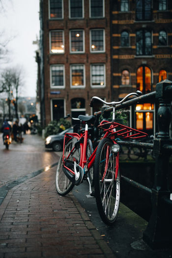 Bicycle parked on street by building in city