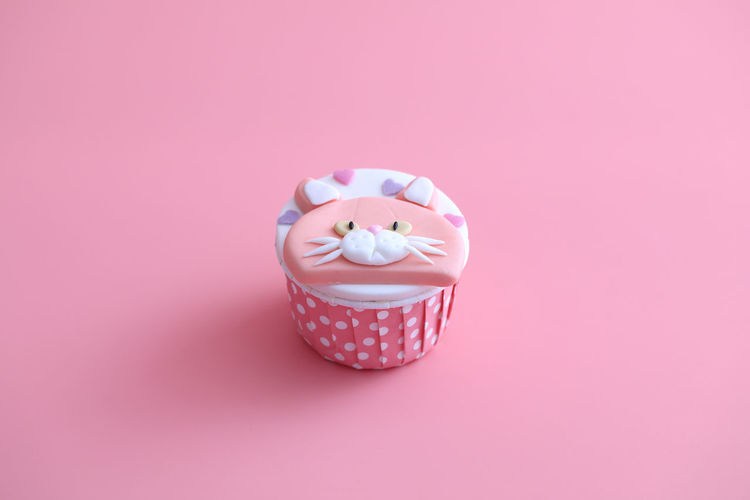 Close-up of cupcakes against pink background