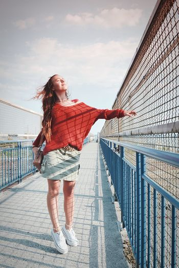 Full length of woman standing on footbridge against sky