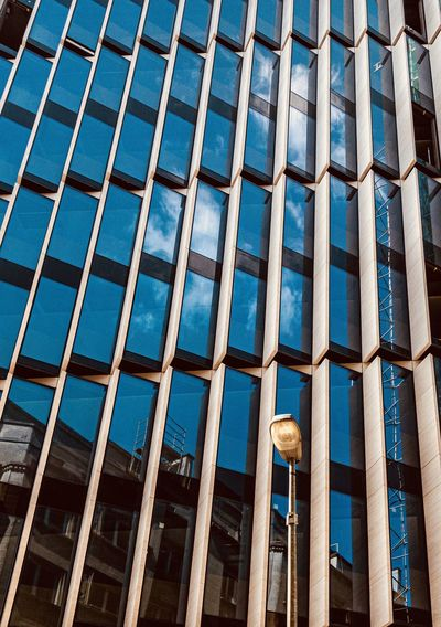 Low angle view of modern glass building in city sky reflecting