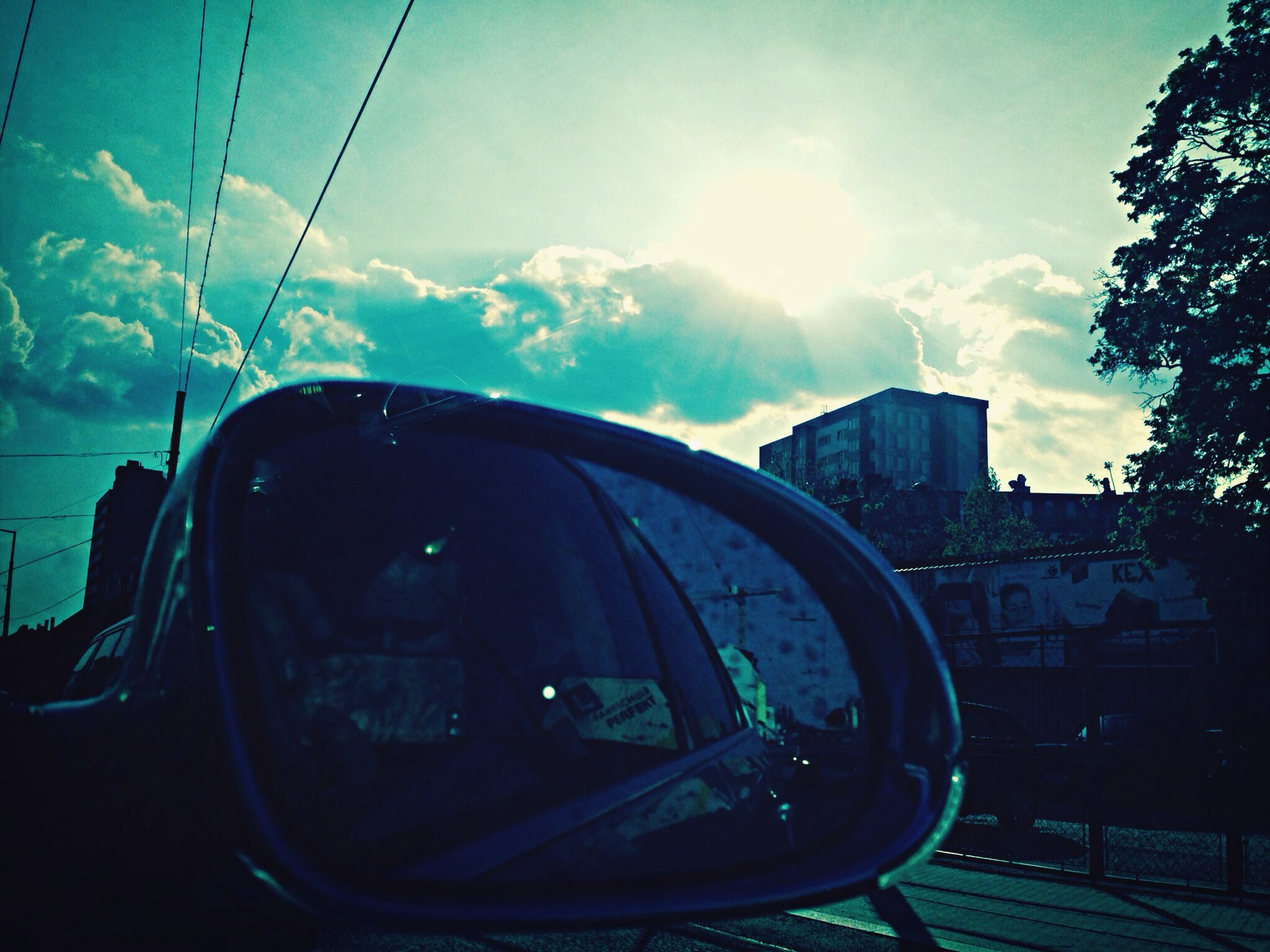 transportation, mode of transport, land vehicle, car, sky, side-view mirror, glass - material, transparent, sunlight, sun, reflection, vehicle interior, building exterior, travel, built structure, sunbeam, windshield, architecture, day, window