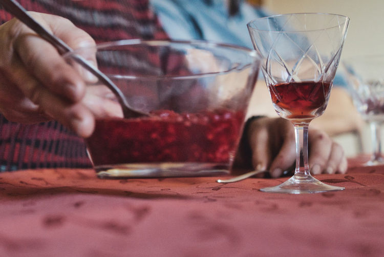 Midsection of man drinking wine at restaurant