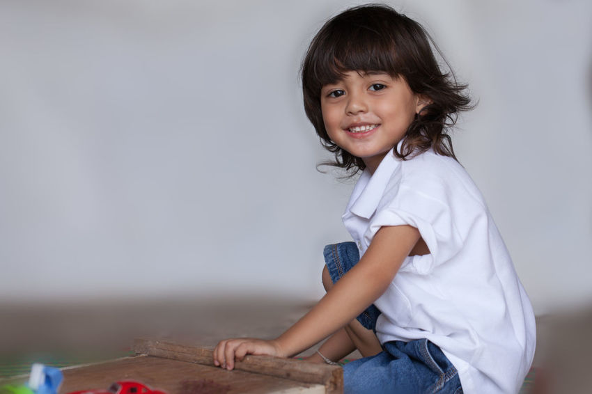 a long hair boy in white shirt and jean playing toy on the ground while waiting for his mom in Mother Day Long Hair, Don't Care. People, Smile, Bangs Boy,  Casual Clothing Cheerful Child Childhood Cute Emotion Females Garland, Girls Hair Hairstyle Happiness Indoors  Innocence Looking At Camera Offspring One Person Play, Kids, Family, Fun, Smile Portrait Sitting Smiling Three Quarter Length Toy, Women