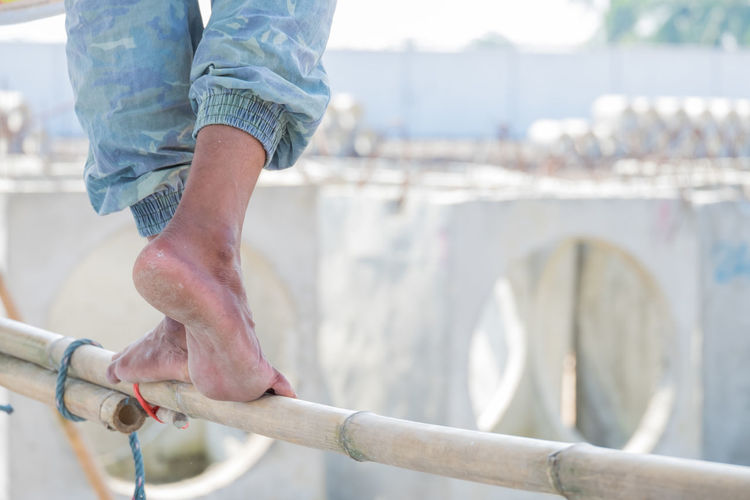 Close up of construction worker's feet treading on a Bamboo Scaffolding, feet with dry heels, cracked skin. One Person Human Body Part Body Part Men Foot Feet Fungus Healthy Heels Human Leg Legs Man Medical Podiatrist Nails Scaffolding Standing Tread Worker Treading Cracked Closeup Care
