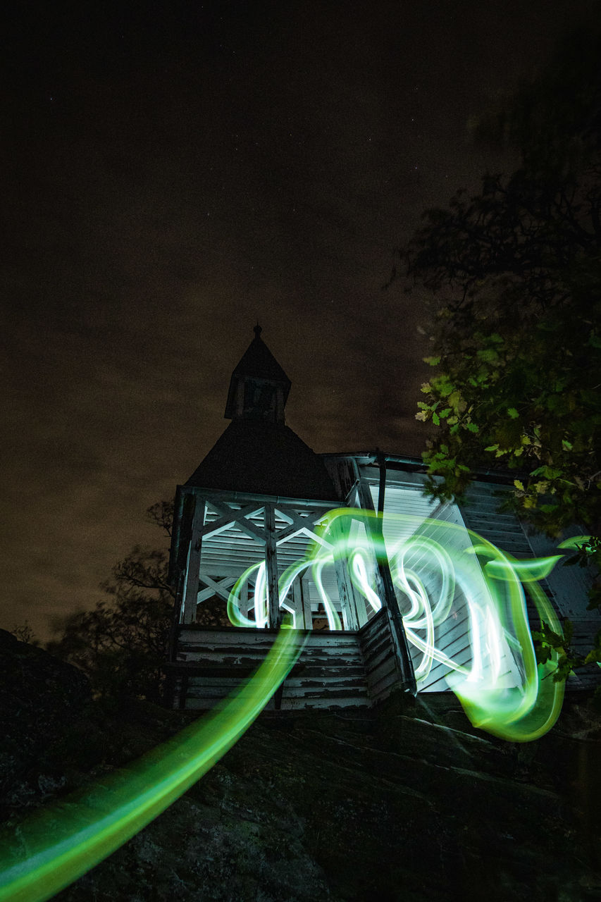 night, plant, illuminated, tree, nature, sky, no people, green color, architecture, built structure, motion, outdoors, light painting, growth, long exposure, cloud - sky, low angle view, land, lighting equipment, dark