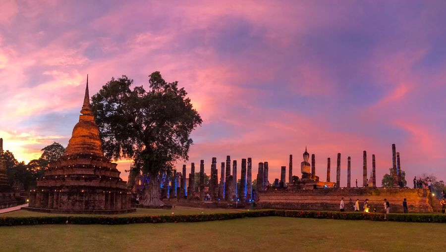 Panoramic view of temple by building against sky during sunset