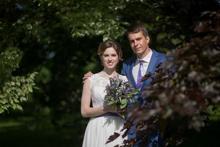 Portrait of bride with bridegroom holding bouquet at park