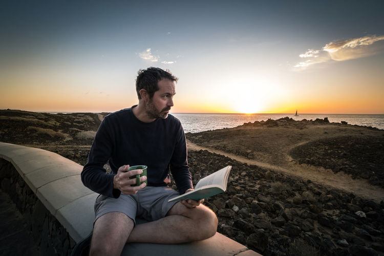 Mid adult man holding book and cup of coffee while sitting against sunset