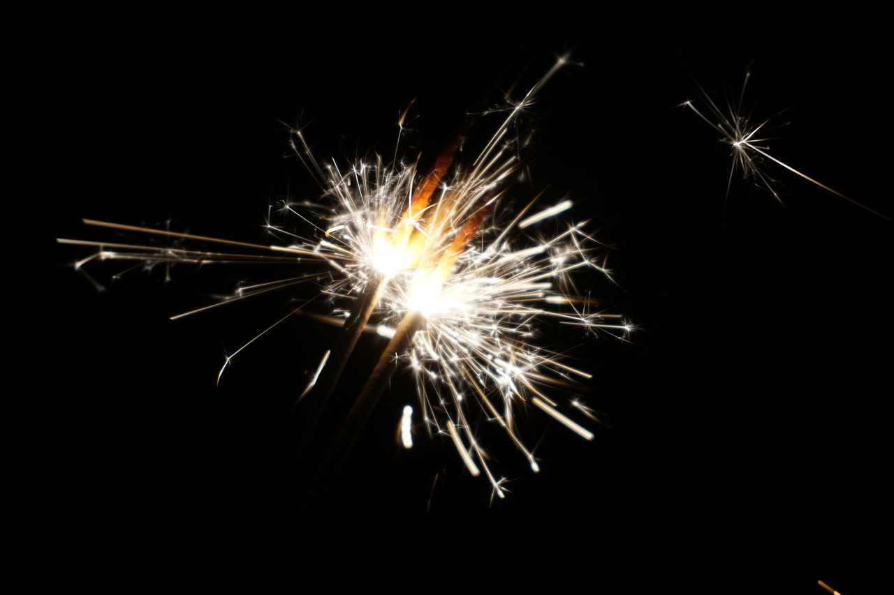 firework - man made object, firework display, night, sparks, celebration, long exposure, illuminated, sparkler, exploding, arts culture and entertainment, glowing, motion, blurred motion, event, firework, low angle view, no people, outdoors, close-up, black background
