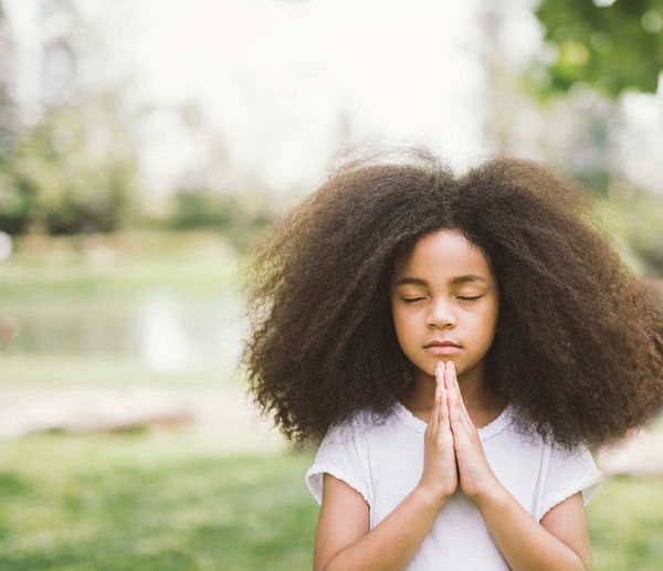 Girl With Frizzy Hair Praying At Park