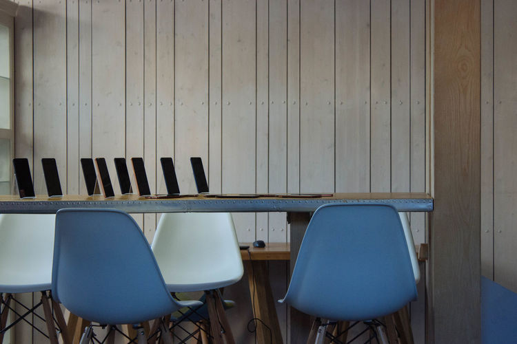 Technologies on table with empty chairs in conference room