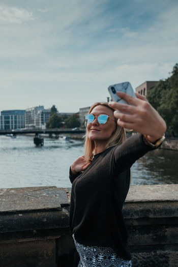 Midsection of woman holding smart phone against sky