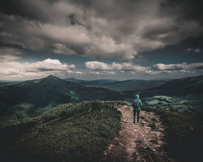 Rear view of mid adult woman walking on mountain against cloudy sky