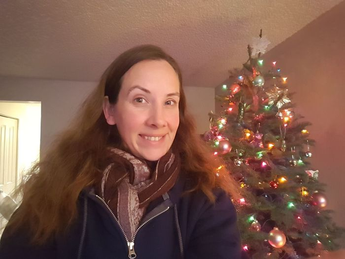 Portrait of young woman with illuminated christmas tree at home