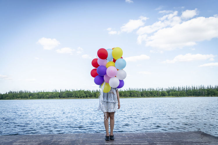 Rear view of woman with balloons standing in lake against sky