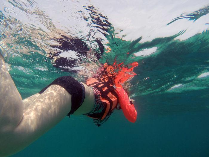 Woman swimming underwater in sea