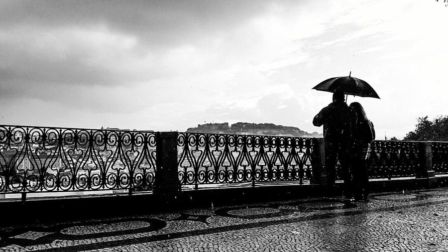 Man with umbrella in city against sky