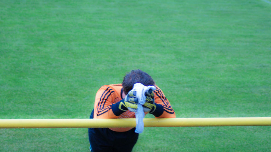 High angle view of man leaning on railing at playing field