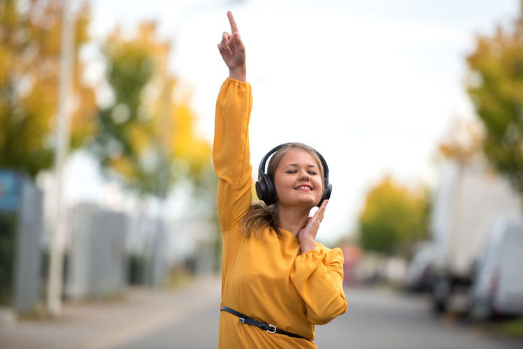 Woman Listening Music While Dancing In City